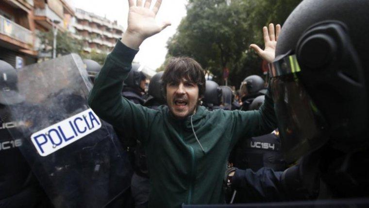 Imatge d'un votant entre policies la jornada de l'1-O a Barcelona