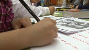 Imatge d'uns alumnes escrivint a classe