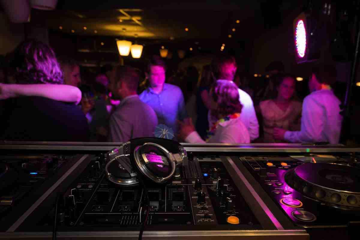 Diverses persones en una discoteca passant-ho bé i uns auriculars en primer pla