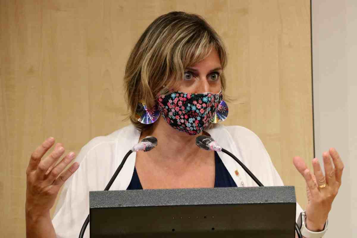 La consellera de Salut, Alba Vergés, amb les mans aixecades, mascareta a la boca i els micròfons davant