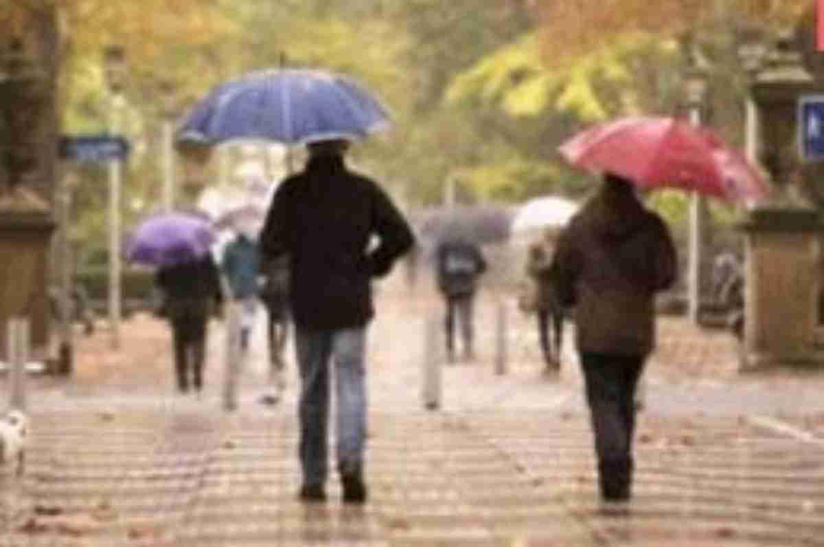 Imatge de dues persones passejant un dia de pluja de tardor