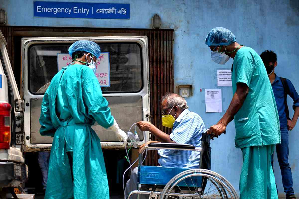 Imatge d'un malalt en cadira de rodes a l'Índia, acompanyat de dos sanitaris