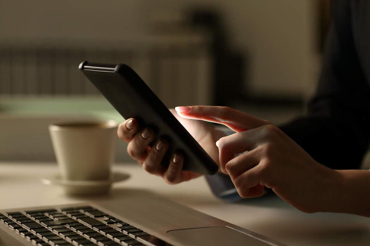 Una persona manipula un telèfon mòbil davant d'un ordinador