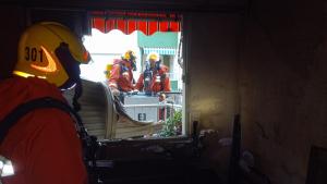 Els bombers des de l'escala en el balcó observen l'incendi