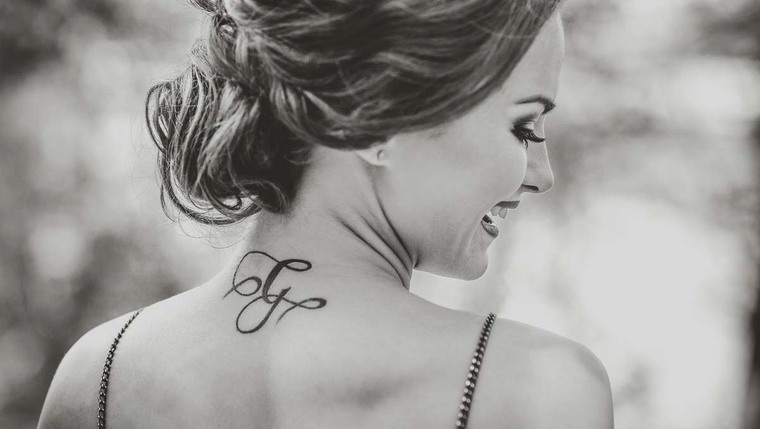 A black and white picture of a woman with her hair up and with a tattoo on her back.