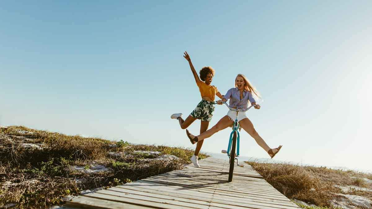 Two girl friends, one on a bike and the other one jumping next to her.