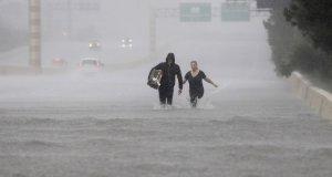 Una pareja camina por la calle en Houston tras el paso del Huracán harvey