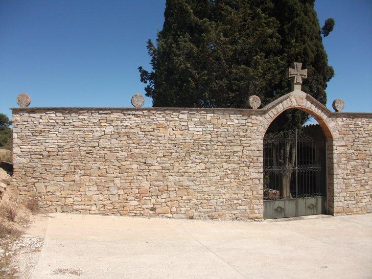 Porta del cementiri de Savallà del Comtat, amb les esteles funeràries sobre el mur.