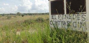 Terrenys on s'ha d'ubicar el Logis Penedès, amb una pintada en contra.