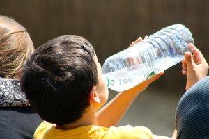 Un nen bebent aigua a l'estiu