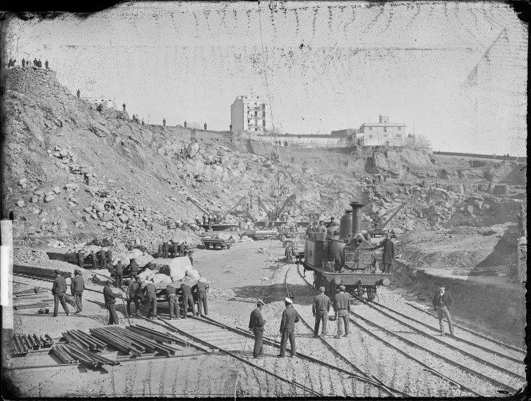 Confinats treballant a la pedrera de les obres del port i vagonetes carregades de pedra, el 1872.