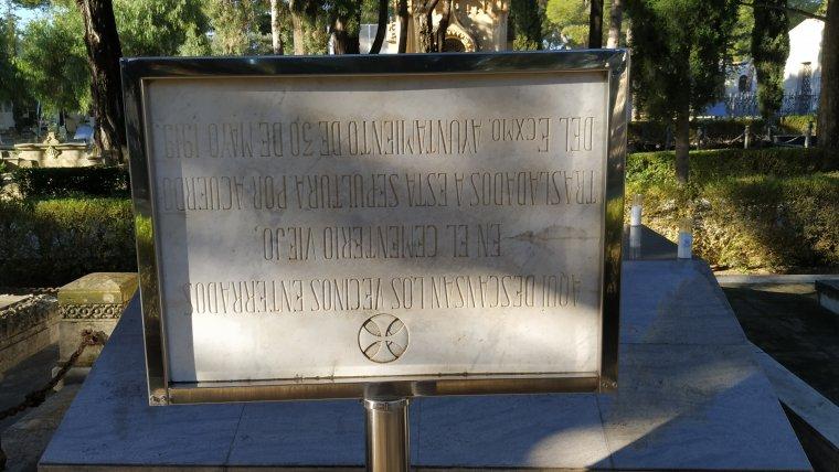 Revers, en castellà i cap per avall, de la placa commemorativa del trasllat del cementiri