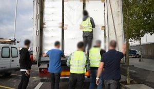 Agents dels Mossos descarregant la droga del camió interceptat en una àrea de servei.