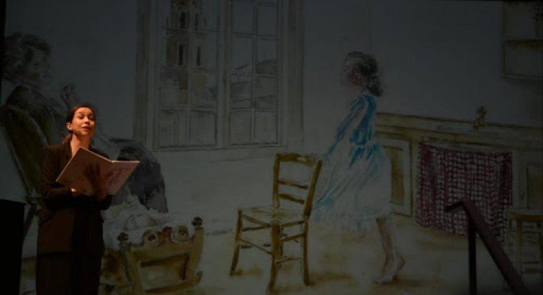 Irene Benavent explica el conte. Al fons una de les aquarel·les de Teresa Llorach on es veu la petita Mauri de puntetes.