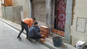 Els manobres tapien les entrades dels immobles després que les portes fossin ineficaces