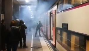 L'operari buidant l'extintor al tren parat a Segur de Calafell.