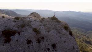 Panoràmica de les muntanyes de la serra de Montsant i un infant dalt del cingle