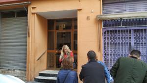 Un grup de veïns discuteixen, a la porta de l'edifici, quines accions emprendre