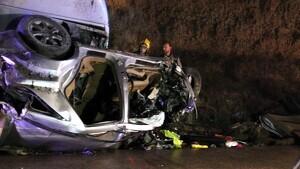 Dos bombers revisen el vehicle que ha quedat atrapat sota la cabina del camió en l'accident mortal a la C-12