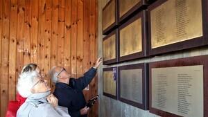 Familiars busquen el nom de Glaussel René, mort en la Batalla de l'Ebre, a les plaques d'homenatge del Memorial de les Camposines