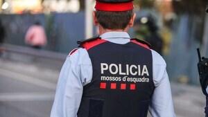 Un agente de los Mossos d'Esquadra vigilando la salida de un colegio en Barcelona