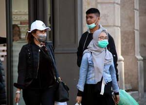 Pla general de ciutadans passejant pels carrers del centre de Barcelona amb mascaretes, l'11 de març del 2020