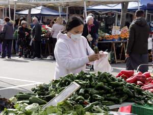 Pla mitjà d'una compradora amb mascareta al mercat dels dissabtes de Lleida, el 14 de març de 2020