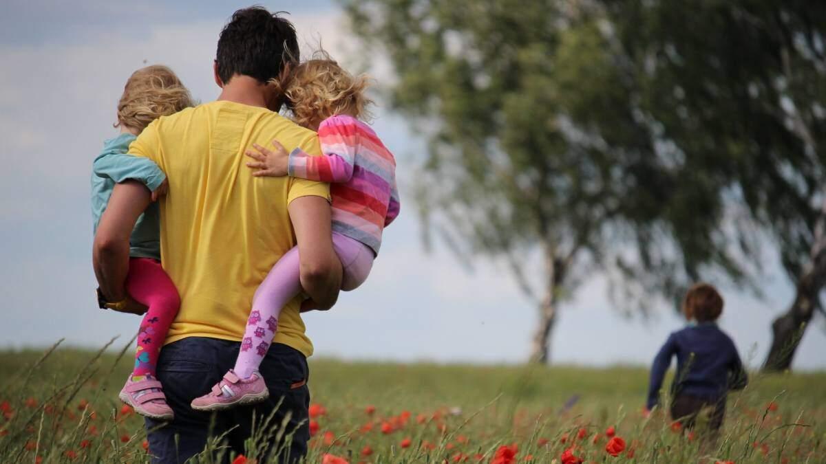 Imatge d'un pare amb els seus fills a coll d'esquenes