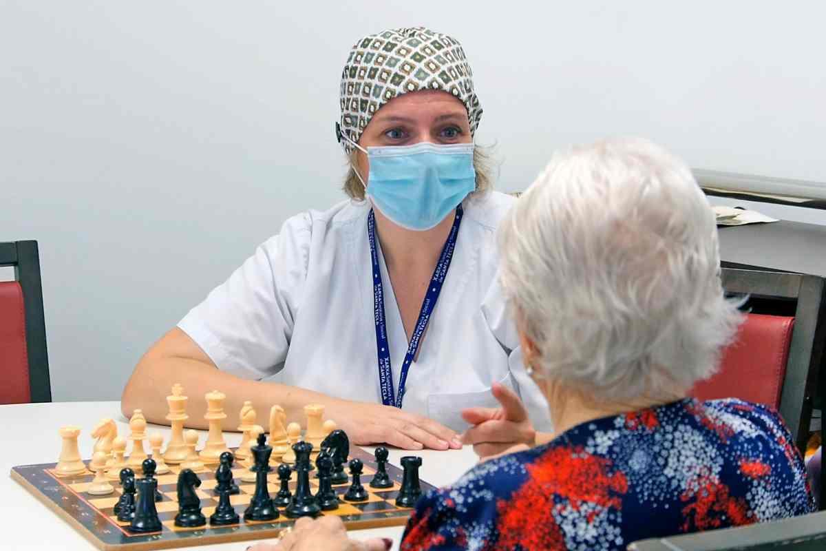 Una sanitària jugant als escacs amb una dona gran