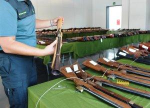 Un agent de la Guàrdia Civil amb una de les armes de l'exposició.