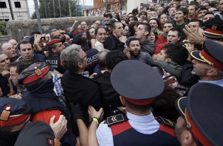 Imatge dels Mossos d'Esquadra durant la votació de l'1 d'octubre entrant en un punt de votació.