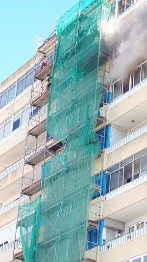 Los vecinos usando el andamio para escapar del daño de las llamas