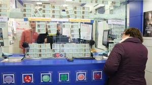 Imagen de una mujer comprando Lotería en una administración