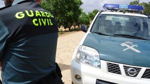 Imagen de archivo de un agente de la Guardia Civil junto a un vehículo oficial