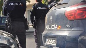Imagen de dos agentes de la Policía Nacional vigilando delante de su coche