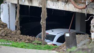 Detalle del aparcamiento sobre el que se ha hundido un parque infantil y una pista deportiva de una urbanización en el barrio de Nueva Montaña de Santander
