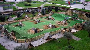 Vista del parque infantil y la pista deportiva que se ha hundido sobre un aparcamiento de una urbanización en el barrio de Nueva Montaña de Santander, este lunes.