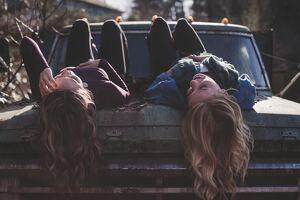 Dos chicas tumbadas hacía arriba sobre el capó de un coche