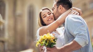 Chico besando en la mejilla a una chica mientras él sujeta a la vez un ramo de flores