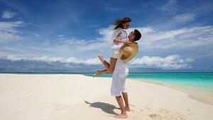 Un chico sujetando a su pareja en brazos al lado de una playa