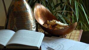 Una mesa donde se puede ver un libro, un plano astrológico y un jarrón