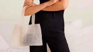 Modelo posando con un bolso de abalorios en color blanco