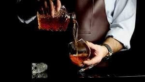 Hombre echando cognac en una copa
