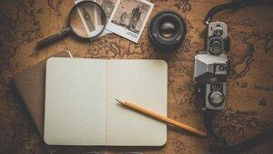 Diversos objetos de viajero: una cámara, un bloc de notas, una lupa, un mapa...