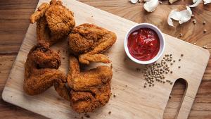 Imagen de un plato de pollo rebozado con salsa al lado