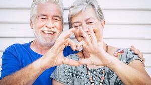 Una pareja mayor haciendo con las manos el símbolo del corazón