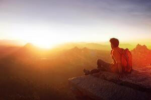 Un hombre sentado al borde de un acantilado mirando la puesta de sol