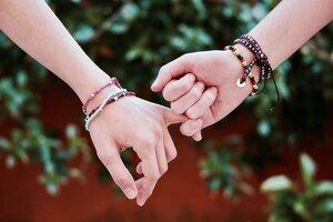 Dos manos cogiéndose del dedo meñique en señal de promesa