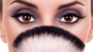 Mujer con los ojos marrones y una brocha de maquillaje