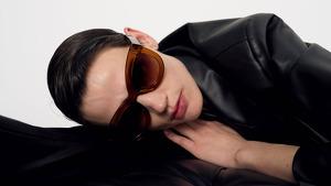 Modelo posando con un traje negro y gafas de sol